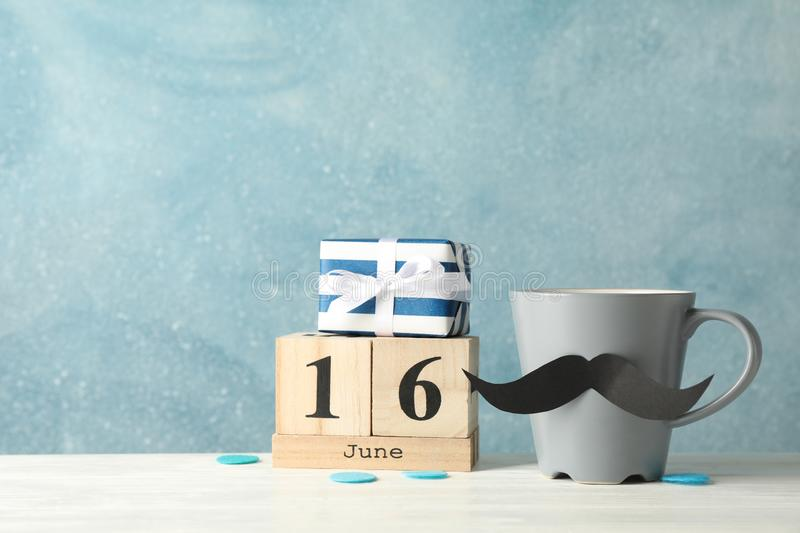 Cup with decorative mustache, gift box and wooden calendar on white table against blue background. Space for text royalty free stock photo