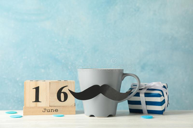 Cup with decorative mustache, gift box and wooden calendar on white table against blue background. Space for text stock photos
