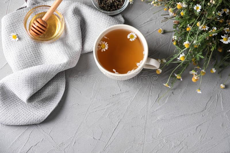 Cup of delicious camomile tea and honey on light table royalty free stock images