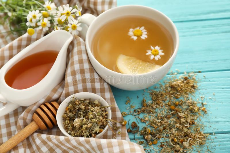 Cup of delicious camomile tea and honey on wooden table stock photos