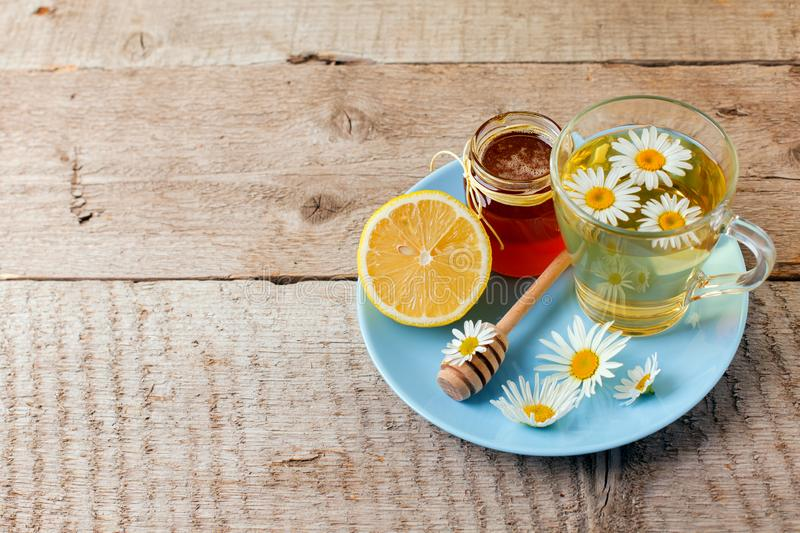 Cup of delicious camomile tea, lemon and honey on wooden table. Seasonal flu cold alternative medicine remedy.  royalty free stock image