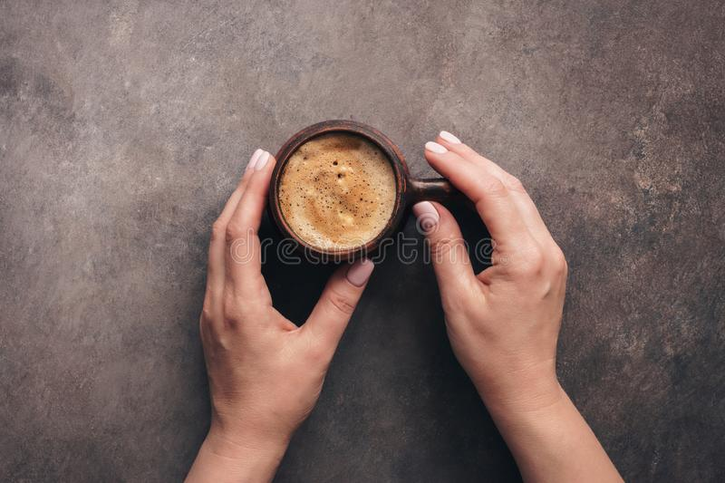Cup of delicious cappuccino coffee in female hands, dark rustic background, top view stock image