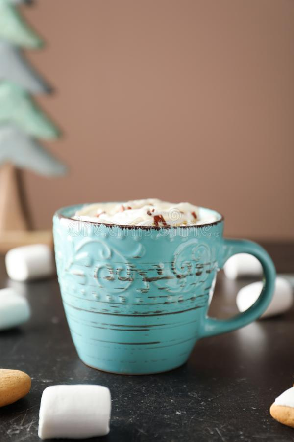 Cup of delicious hot cocoa with sweets on table stock image