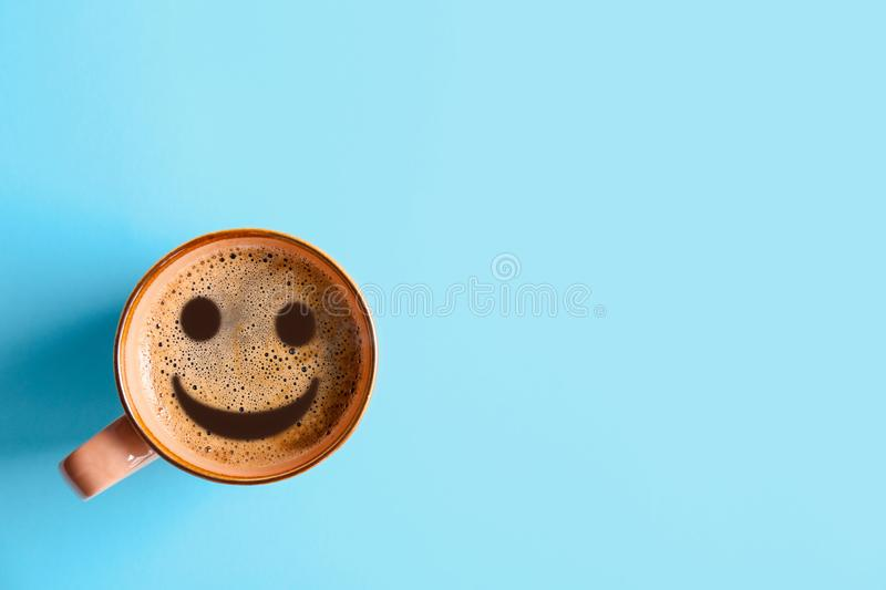 Cup of delicious hot coffee with foam and smile on color background, top view. Happy morning, good mood, inspiration royalty free stock photo