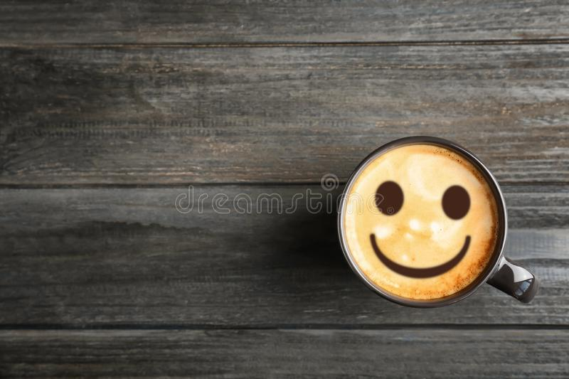 Cup of delicious hot coffee with foam and smile on wooden background, top view. Happy morning, good mood, inspiration stock photo