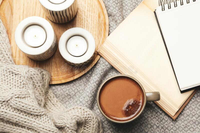 Cup of delicious hot winter drink and candles on grey fabric, flat lay. Winter drink. Cup of delicious hot winter drink and candles on grey fabric, flat lay royalty free stock images