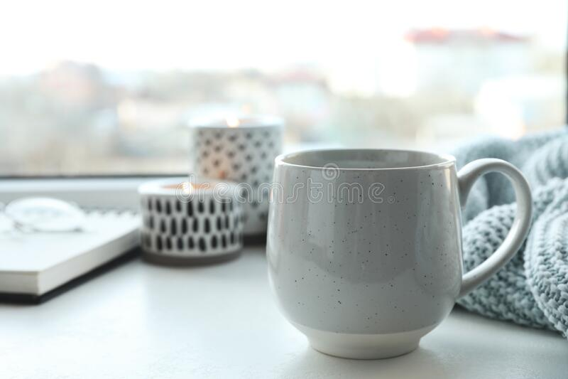 Cup of delicious hot winter drink on window sill. Indoors royalty free stock image