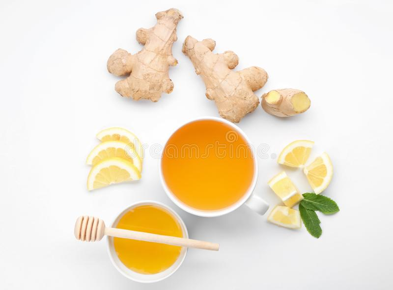 Cup of delicious tea with ginger, lemon and honey on white background stock images