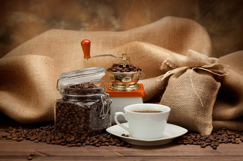 Cup of espresso, beans and grinder. Coffee - cup of espresso, beans and grinder royalty free stock photography