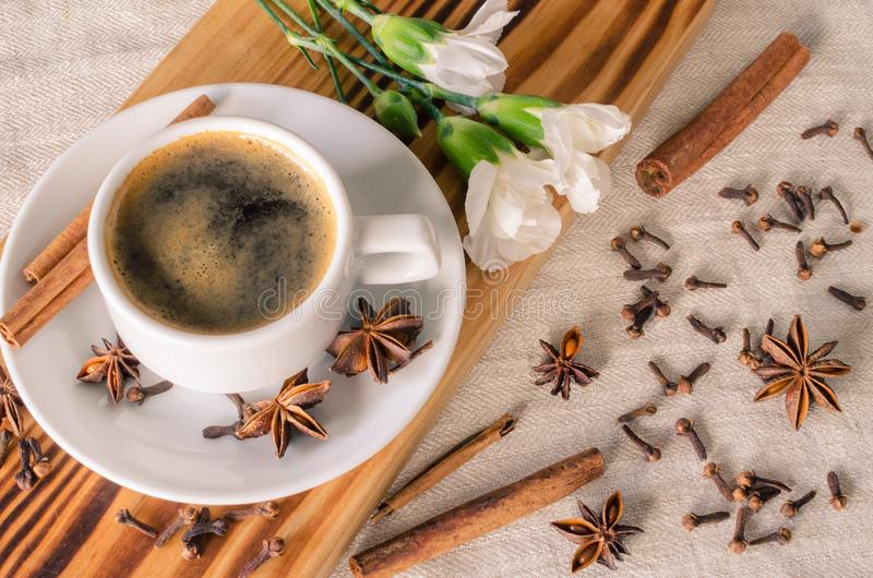 A cup of espresso, cinnamon sticks, anis stars and white carnations on wooden desk and textile background.  Good morning. A cup of espresso, cinnamon sticks stock image