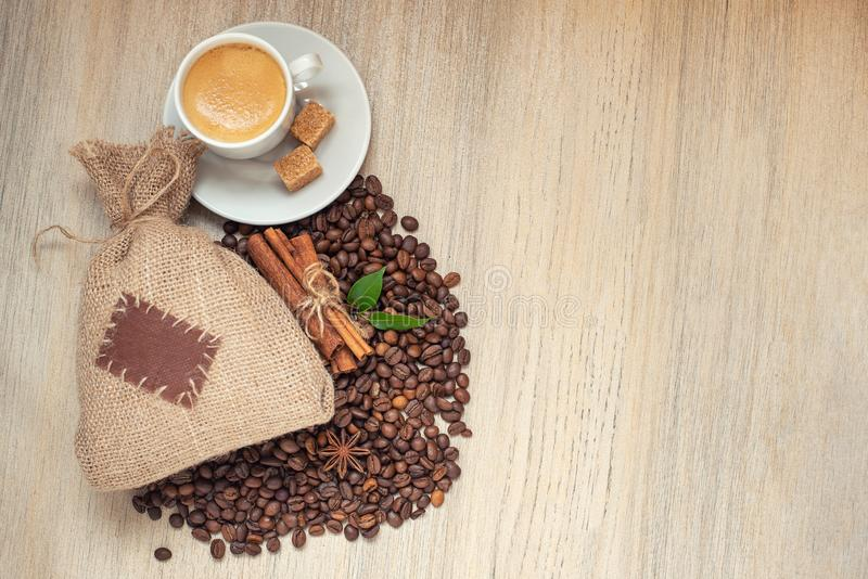 Cup with espresso with coffee beans, burlap sack and cinnamon on light wooden background stock images