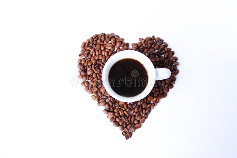 Cup of espresso and coffee beans on white background. The view from the top. A Cup of espresso on coffee beans, laid out in the form of a heart. The view from royalty free stock photos