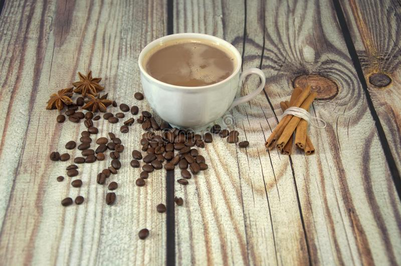 A cup of espresso, coffee beans, star anise and cinnamon on the table. Close-up stock images