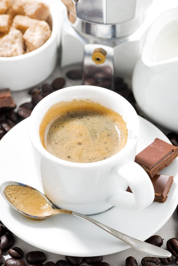 Cup of espresso, coffee beans and sweets, closeup vertical. Cup of espresso, coffee beans and sweets,vertical royalty free stock photography