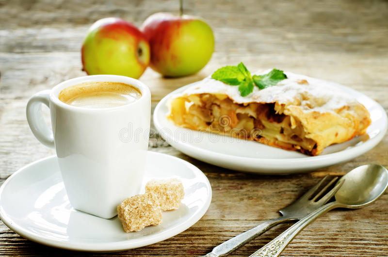 Cup espresso coffee with cane sugar and apple strudel royalty free stock image