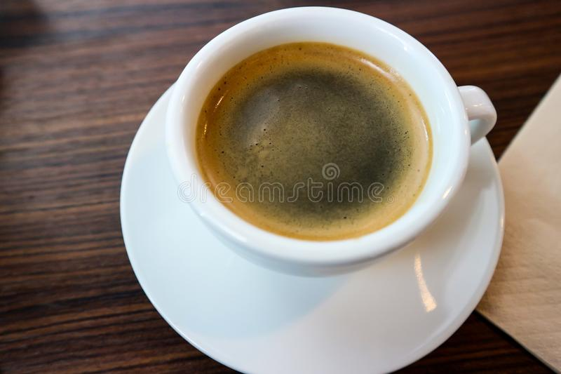 A cup of Espresso coffee. On the wood table in soft focus royalty free stock image