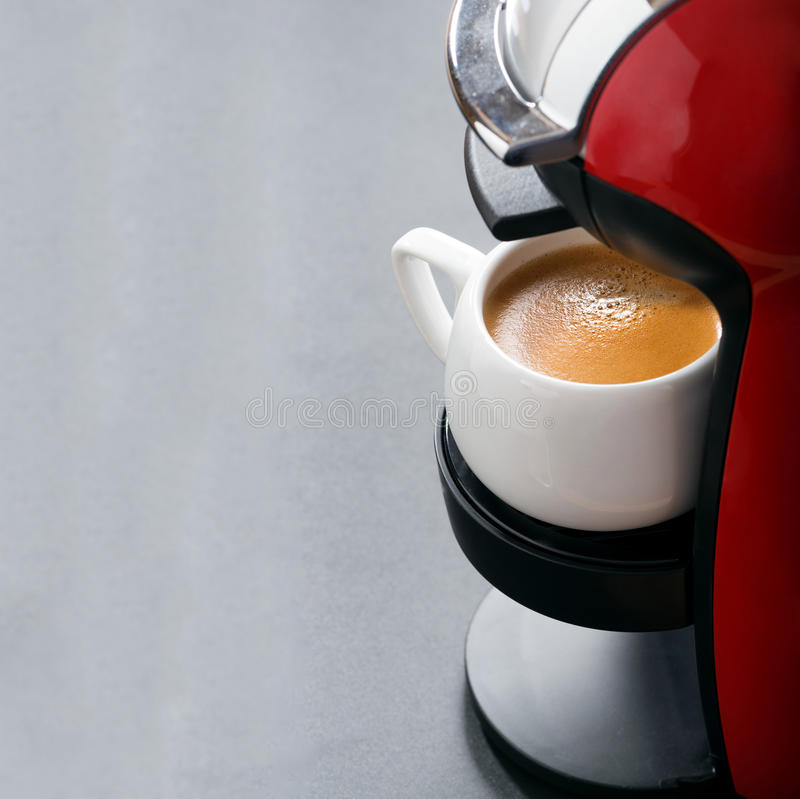 Cup of espresso in the coffee machine and space for your text stock photography