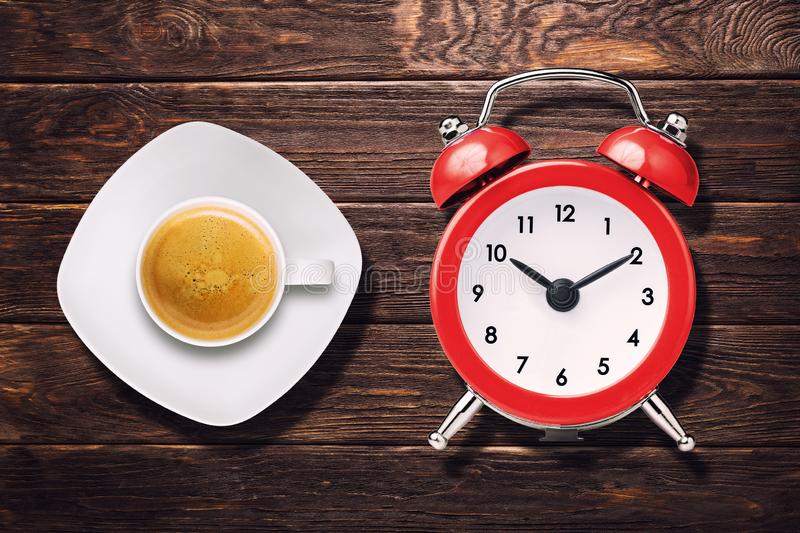 Cup of espresso coffee and vintage clock alarm on wooden table top view.  stock images