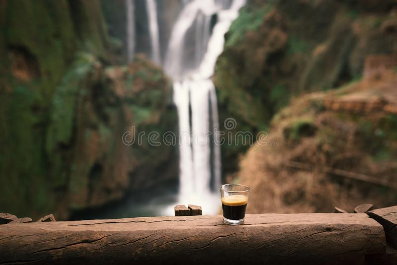 Cup of espresso coffee on a wood against the waterfalls in Morocco - Ouzoud falls. Natural vintage background. Beautiful view from stock image