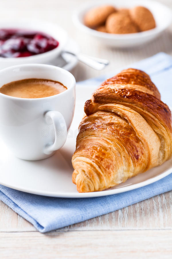 Cup of espresso and croissant stock images