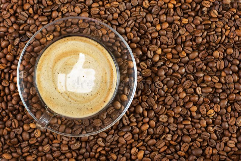 Cup of espresso with like sign on coffee foam on coffee beans background. With copy space stock photo
