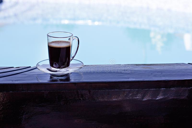 A cup of espresso and a pool in the background. Morning coffee. Summer Breakfast. Coffee at the resort royalty free stock images