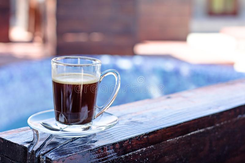 A cup of espresso and a pool in the background. Morning coffee. Summer Breakfast. Coffee at the resort royalty free stock photography