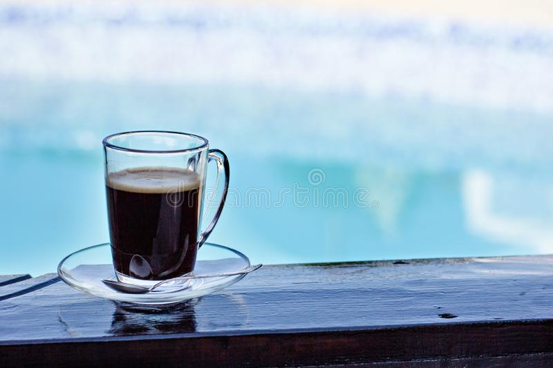 A cup of espresso and a pool in the background. Morning coffee. Summer Breakfast. Coffee at the resort stock image