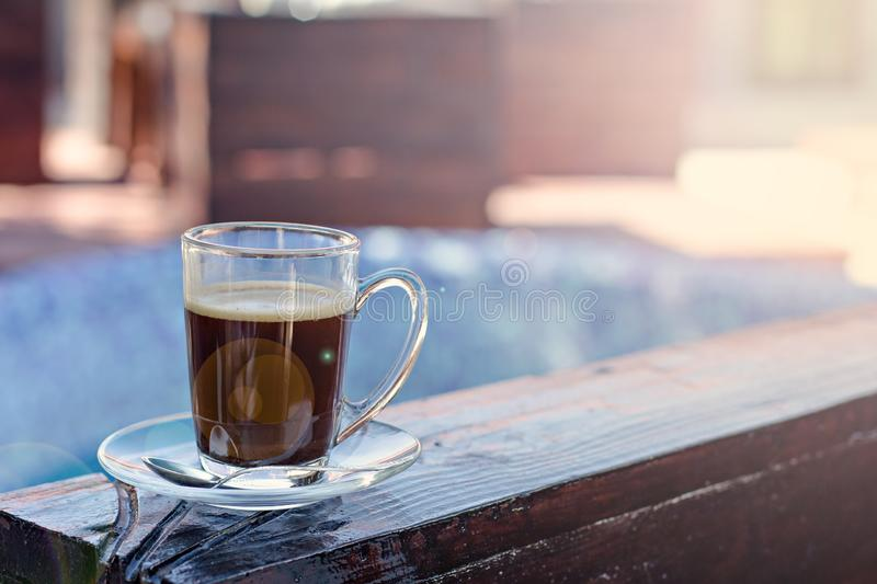 A cup of espresso and a pool in the background. Morning coffee. Summer Breakfast. Coffee at the resort royalty free stock photos