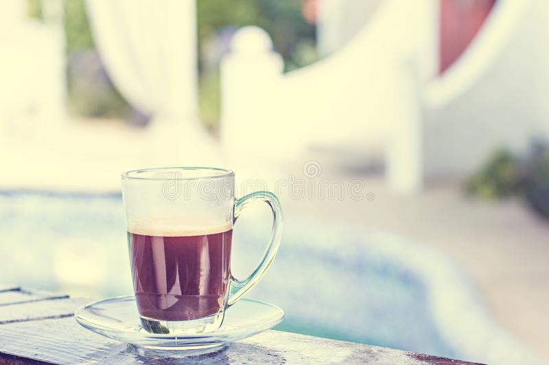 A cup of espresso and a pool in the background. Morning coffee. Summer Breakfast. A cup of espresso and a pool and a white building in the background. Morning stock photography