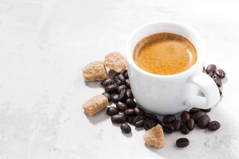 Cup of espresso and sugar on a white table, closeup. Horizontal stock photos