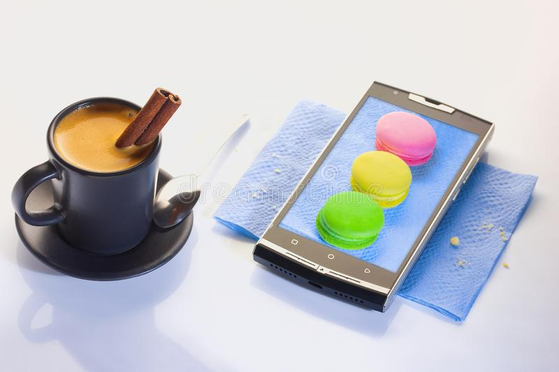 A cup of espresso with a tube of cinnamon. Dessert on a paper napkin in a smartphone. Pasta brownies, red, green yellow. stock image