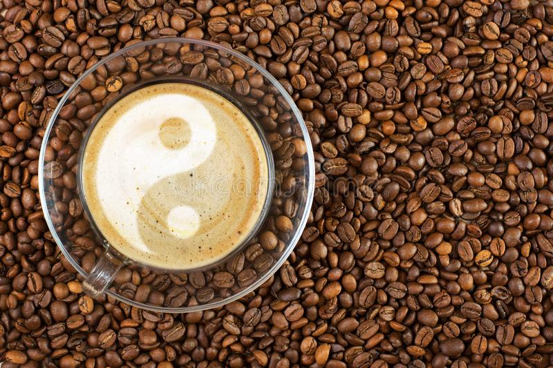 Cup of espresso with yin-yang sign on coffee foam on coffee beans background. With copy space royalty free stock photography