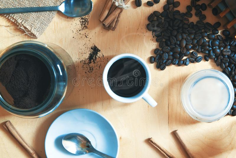 Cup with expresso cafe on a rustic wooden table. Next, some ground coffee and beans with cinnamon. Overhead shot stock photos