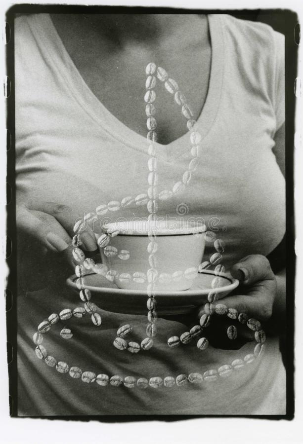 A cup in female hands and a still-life of coffee beans. A true multi-exposure. Attention! The image contains granularity and other artifacts of analog royalty free stock images