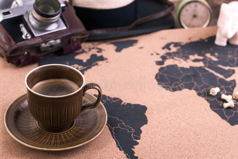A cup of fragrant coffee on the map, an old camera and a route p royalty free stock photography