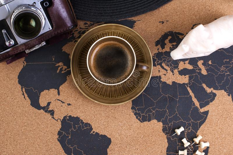 A cup of fragrant coffee on the map, an old camera and a route p stock photo
