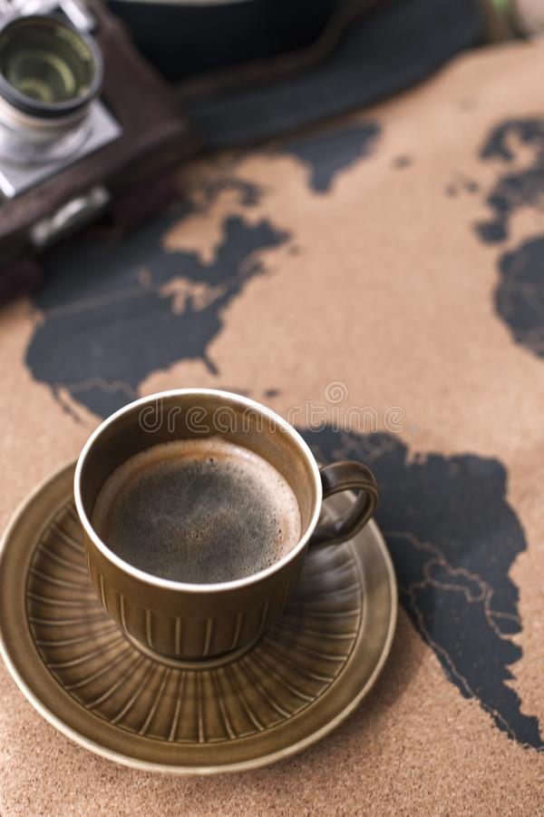 A cup of fragrant coffee on the map, an old camera and a route p royalty free stock photo