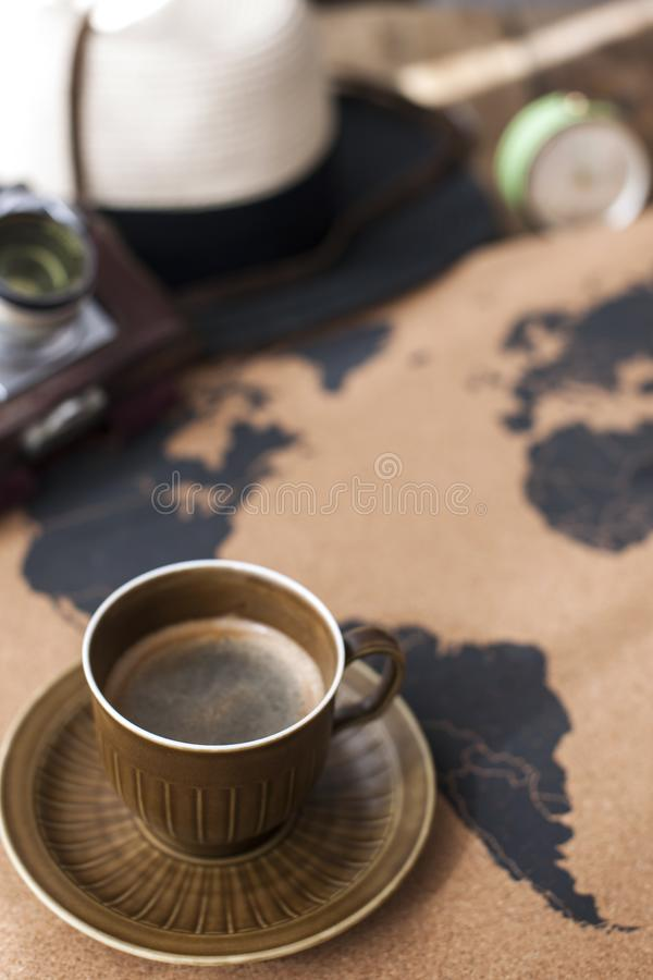 A cup of fragrant coffee on the map, an old camera and a route p stock images