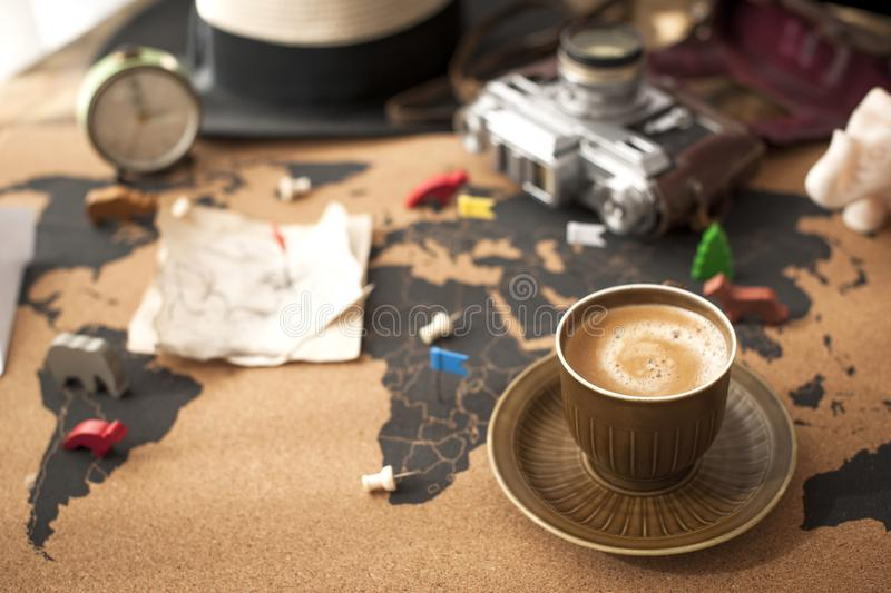A cup of fragrant coffee on the map, an old camera and a route plan, a vintage photo. Travel and holidays. Copy space royalty free stock photography