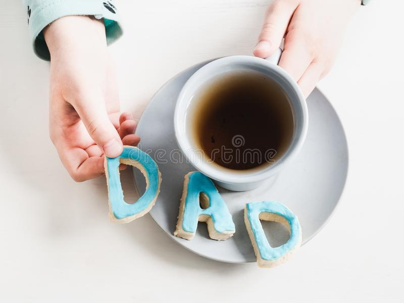Cup of fragrant tea and biscuits in the form of letters D A D royalty free stock photo