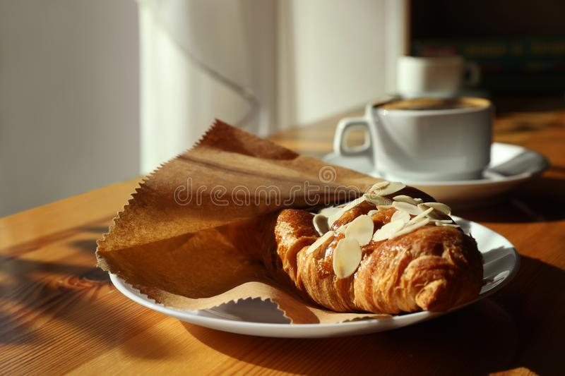 Cup of fresh aromatic coffee and croissant at table. In cafe royalty free stock photo