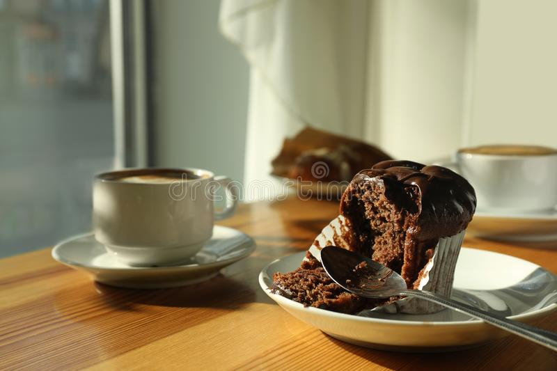Cup of fresh aromatic coffee and cupcake at table. In cafe stock image