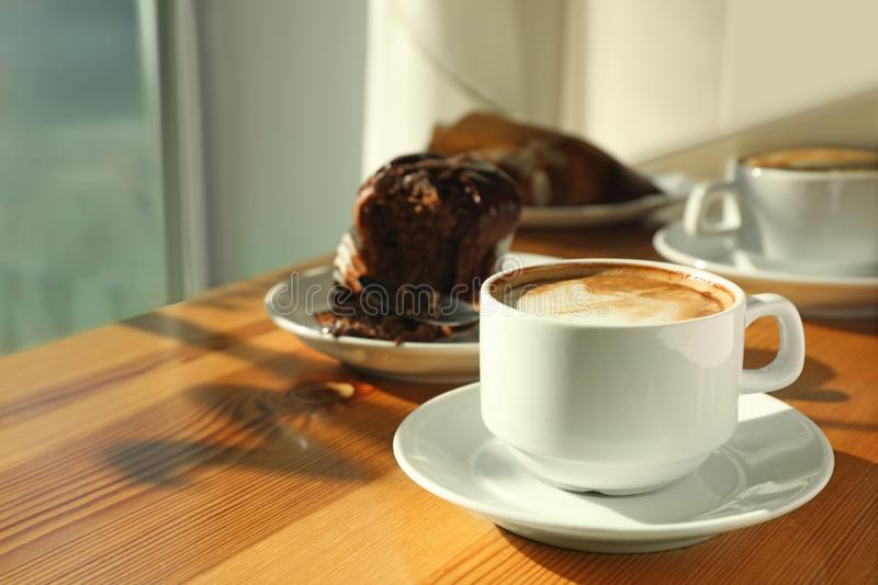 Cup of fresh aromatic coffee and cupcake at table. In cafe stock photos