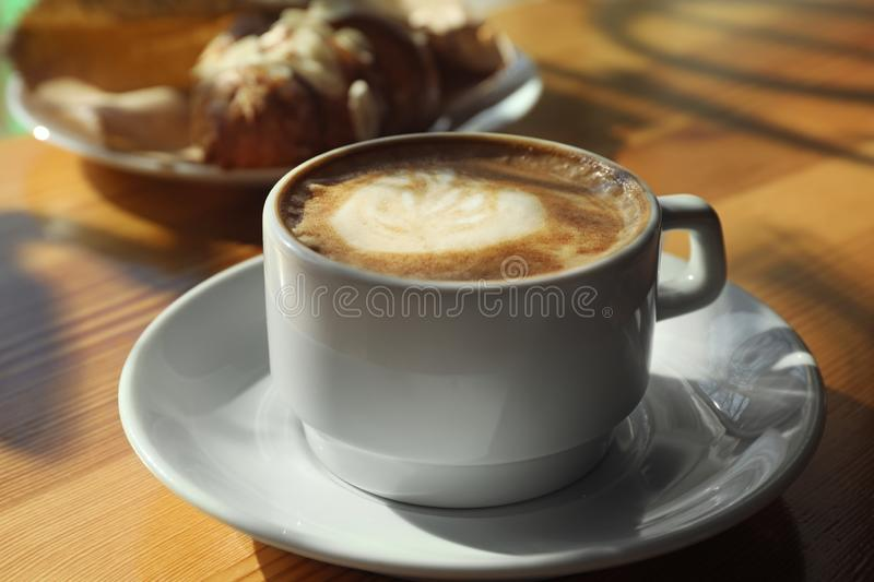 Cup of fresh aromatic coffee at table. In cafe royalty free stock photos