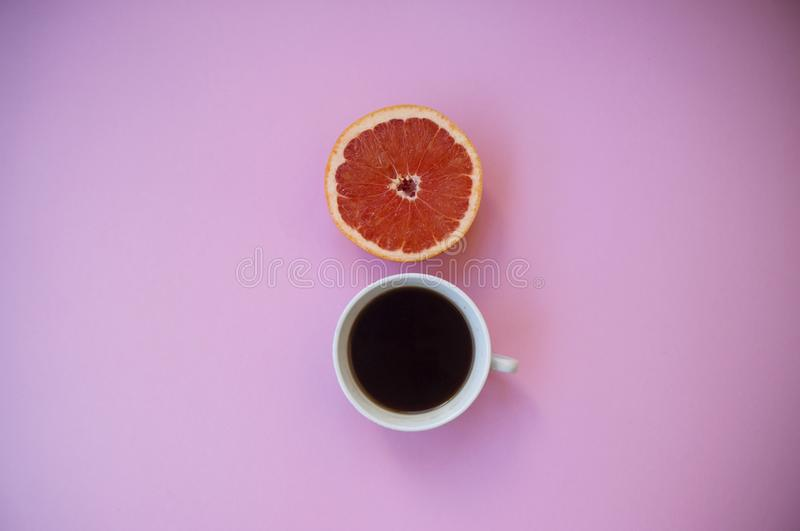 A cup of coffee on and a half of grapefruit on pink background. stock images