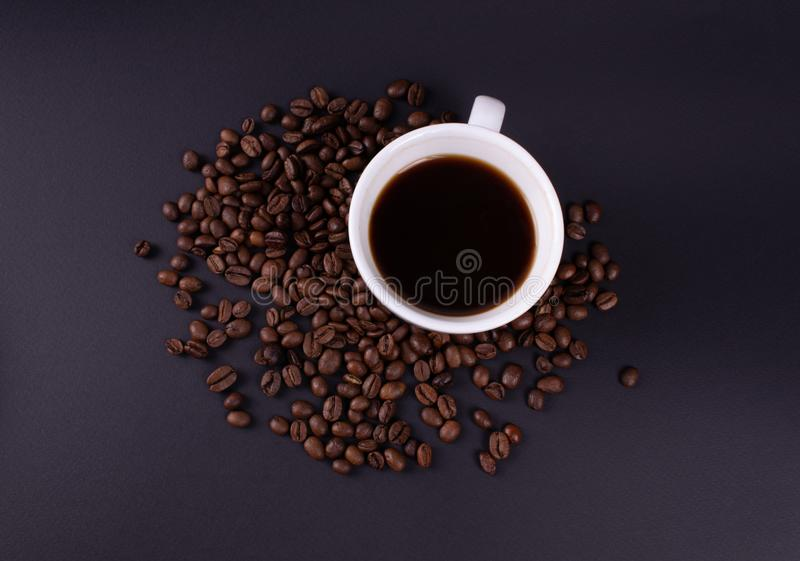 A cup of fresh brewed coffee with coffee beans photo from above stock image