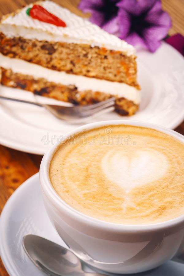 Cup of fresh cappuccino coffee with delicious piece of carrot cake on the wooden table stock photo