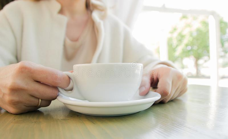 Cup of fresh cappuccino coffee in female hands on the table in summer cafe stock image