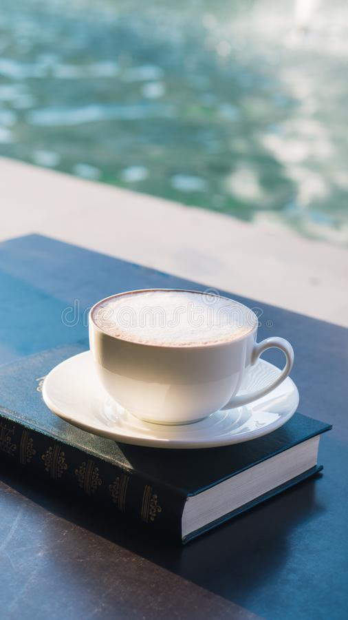 A cup of fresh coffee and a book. Selective focus. Latte or cappuccino stock photo